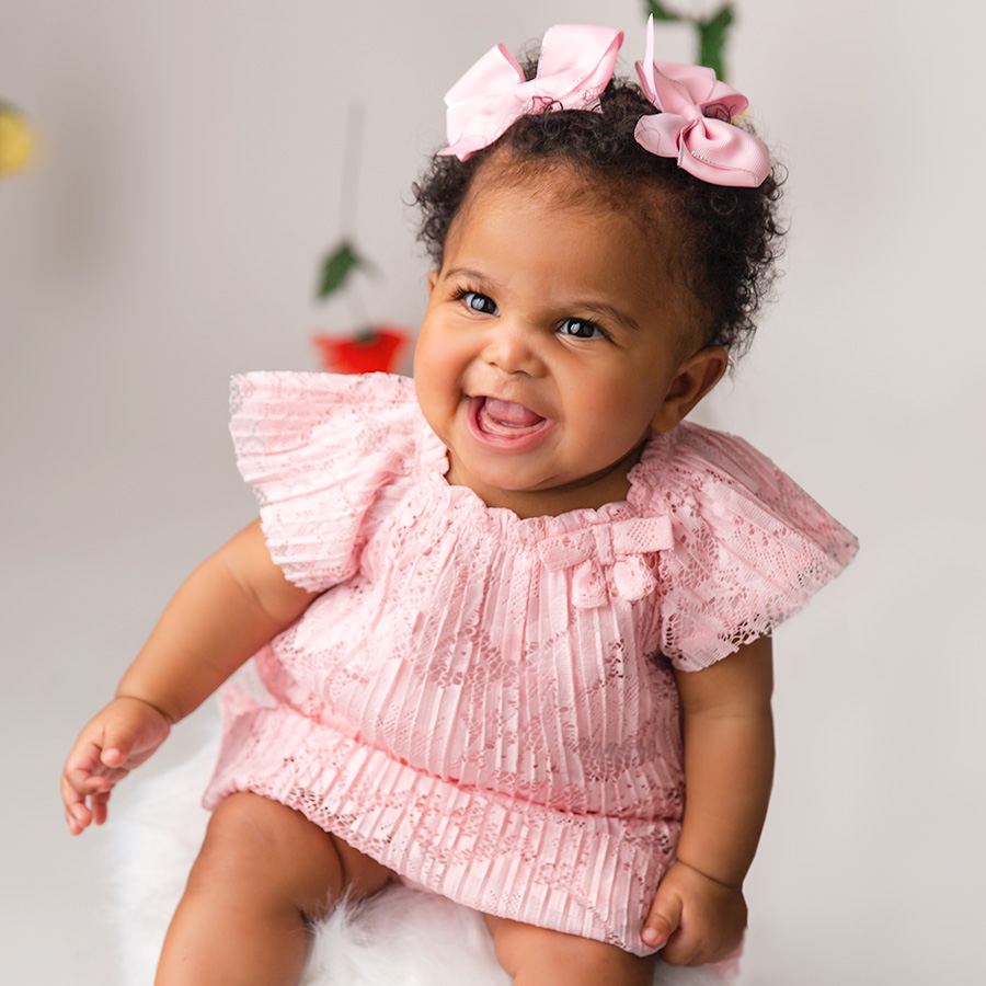 baby girl laughing in pink pace dress with pink bows| DMV sitter session6 month sitter photo session