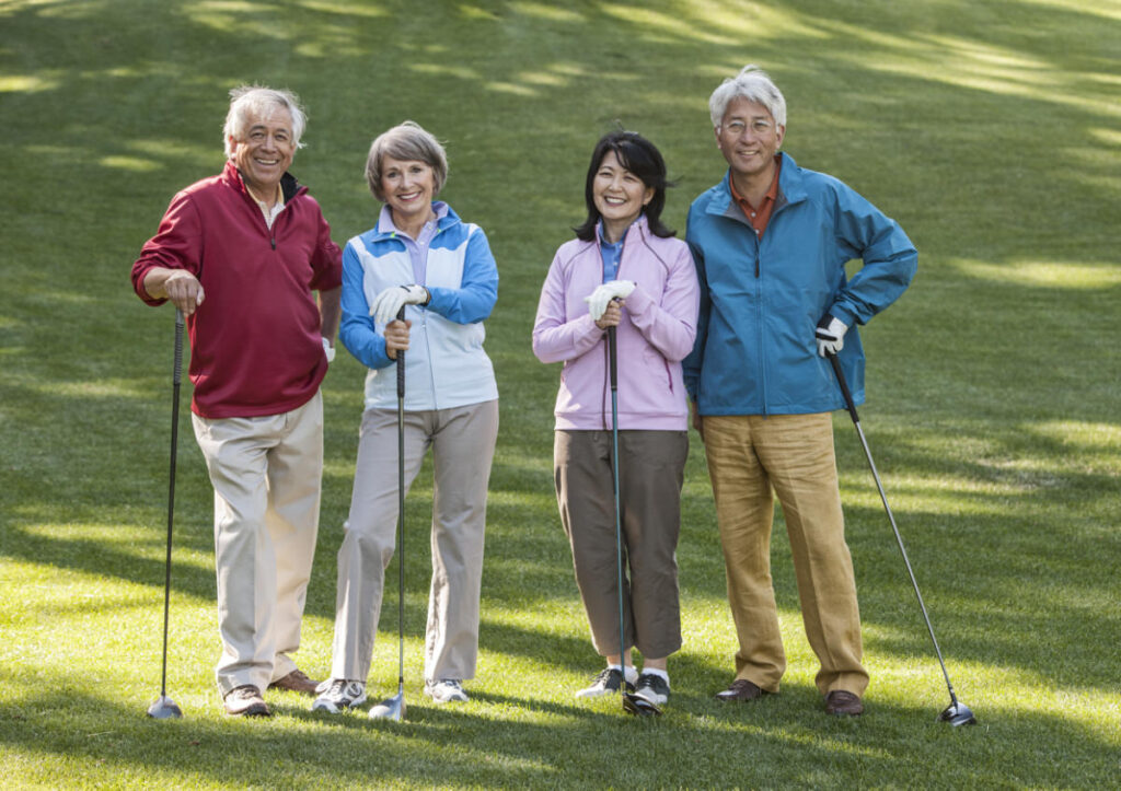 Two young senior golfing couples on the course and ready to play, retirement community, independent living