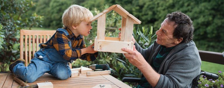 A young boy and his grandfather hold up a birdfeeder they have built and look at each other through the sides