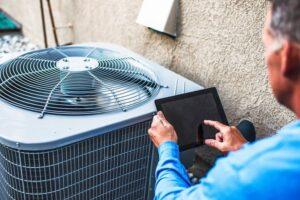 HVAC-contrator-diagnosing-air-conditioning-unit