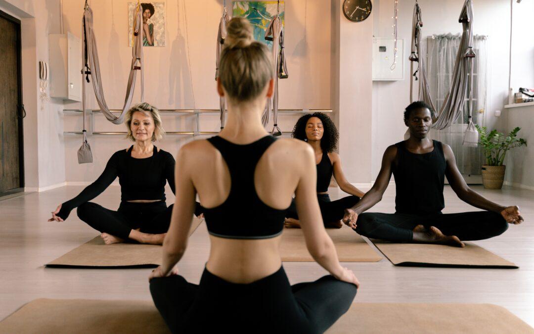 Woman in Black Sports Bra and Black leggins doing yoga facing three persons