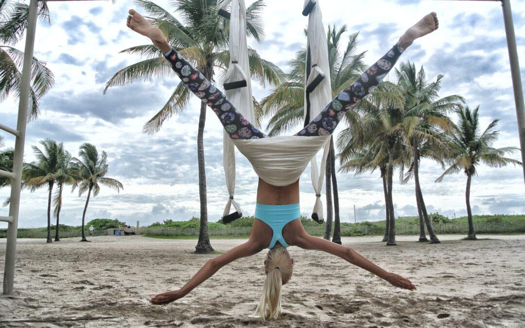 A woman wearing sky blue racer back doing anti-gravity yoga