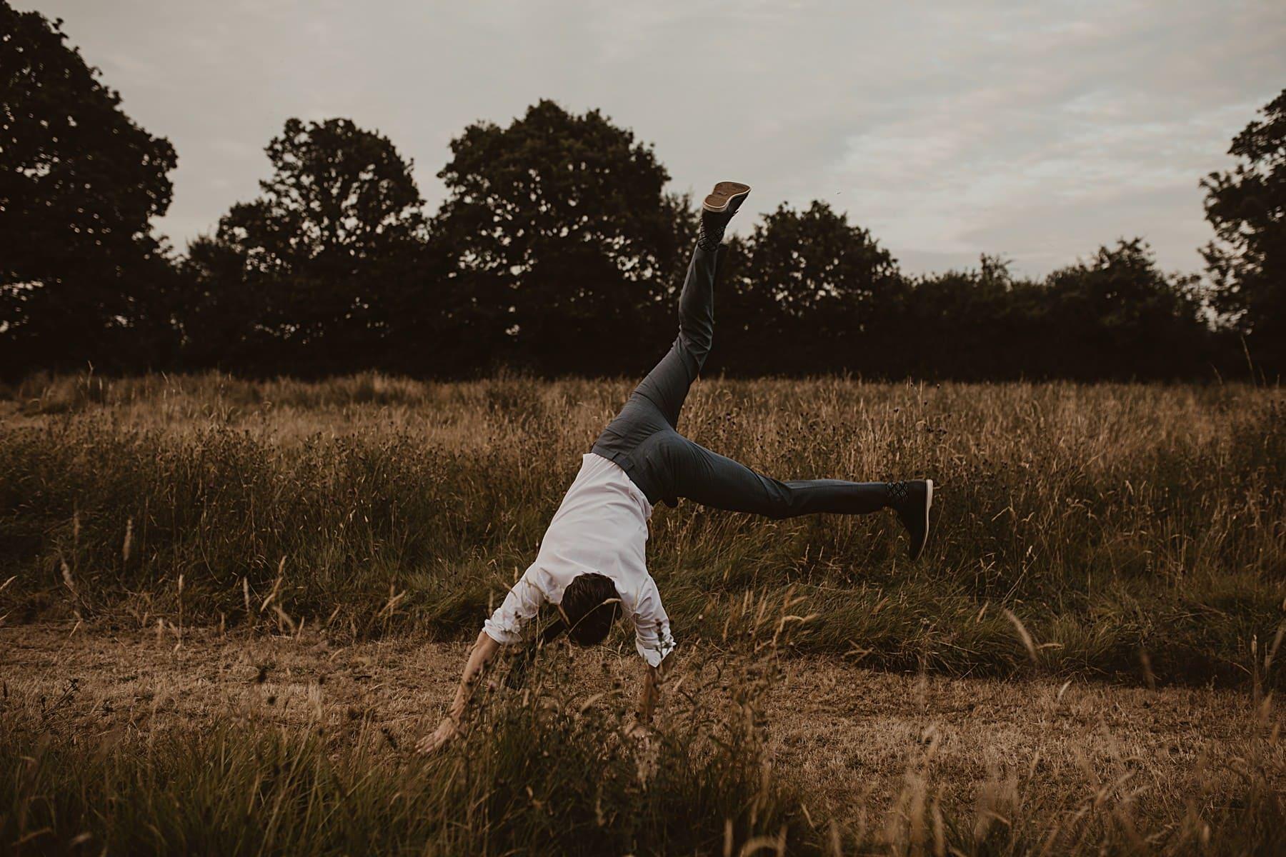 Groom cartwheel in meadow