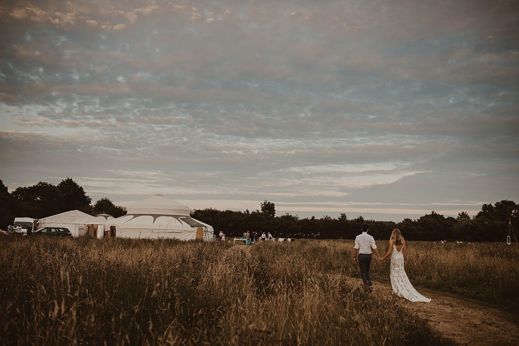 Bride and Groom walking to yurt, sunset
