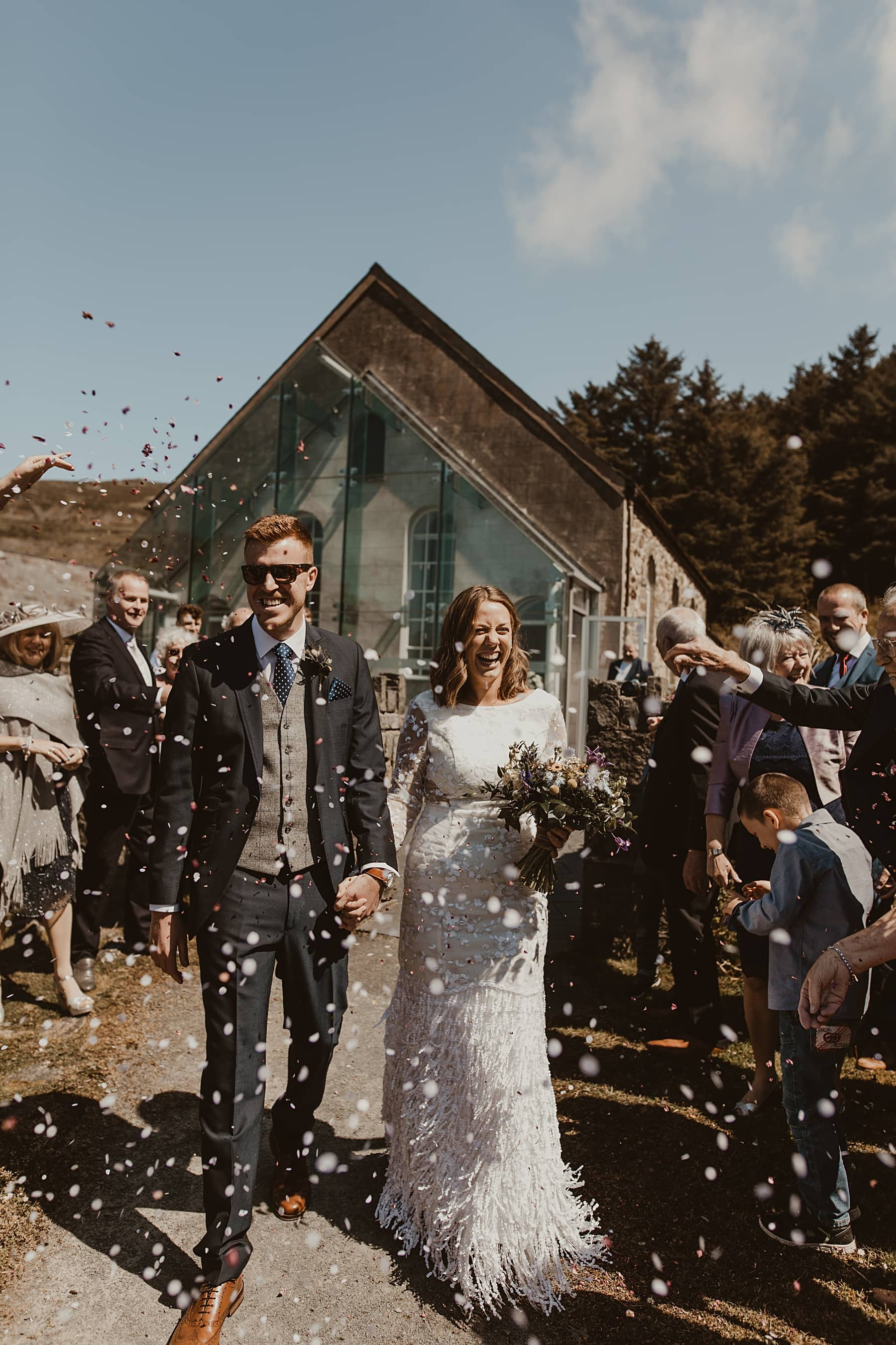 bride and groom walking and laughing through confetti