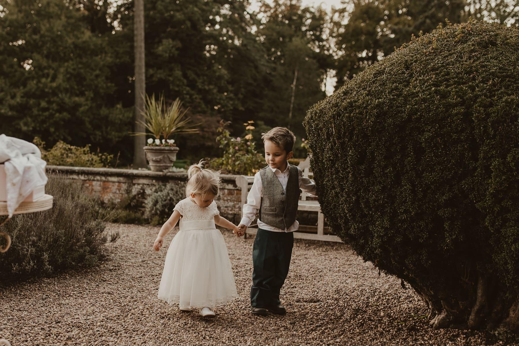 children holding hands walking through gardens