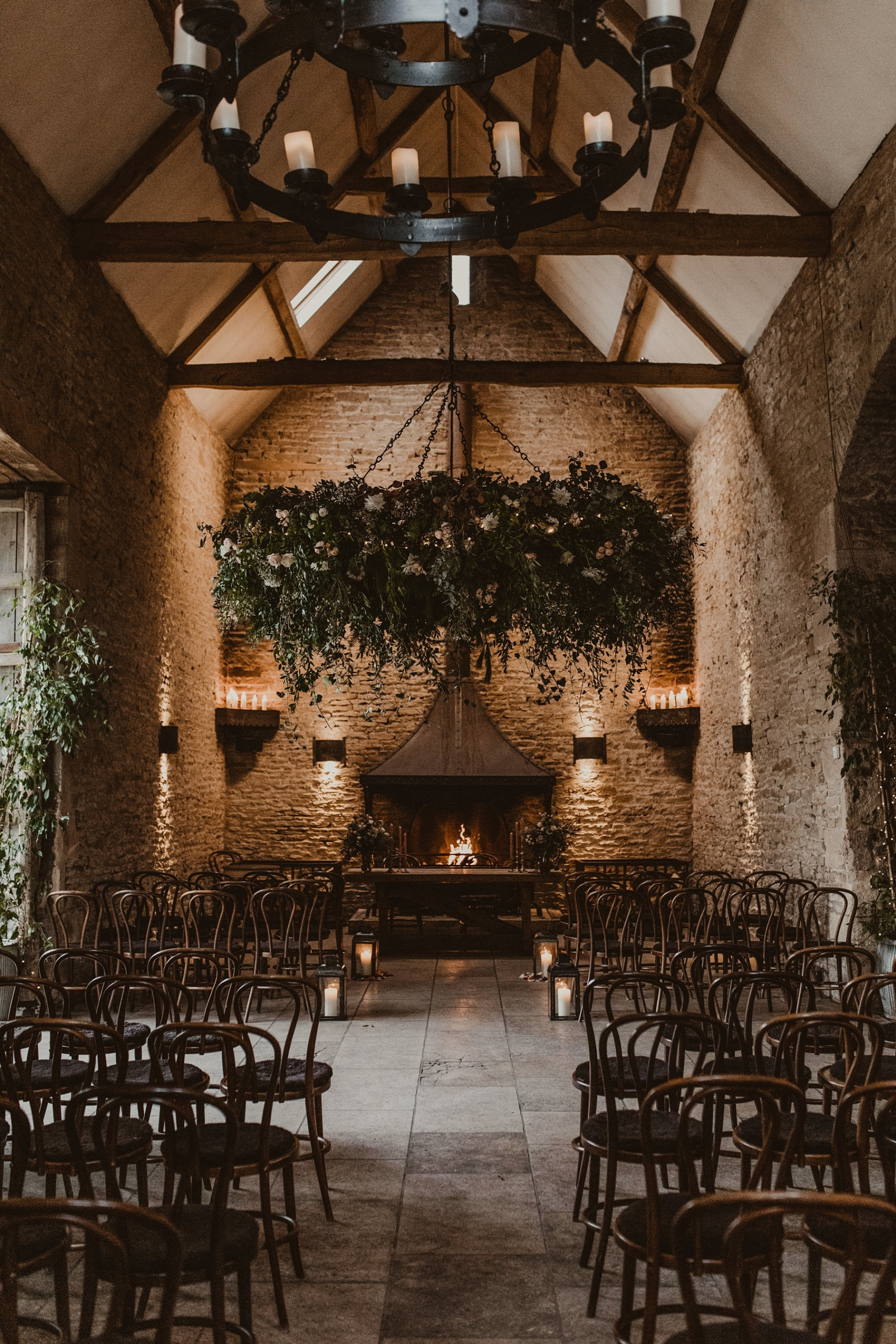 Foliage installation decorating ceremony room with fireplace at Stone Barn
