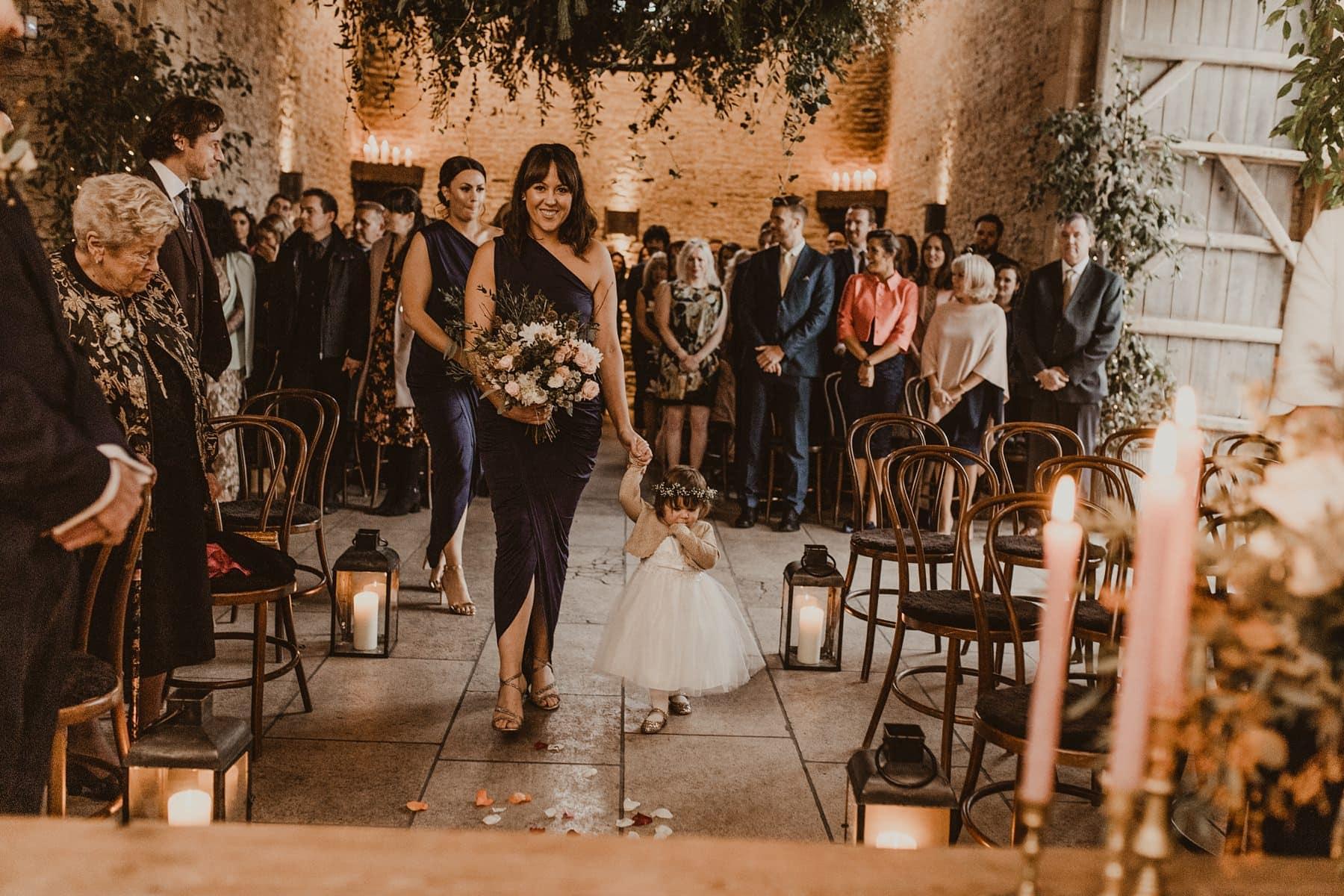 Bridesmaid and flower girl walking down isle