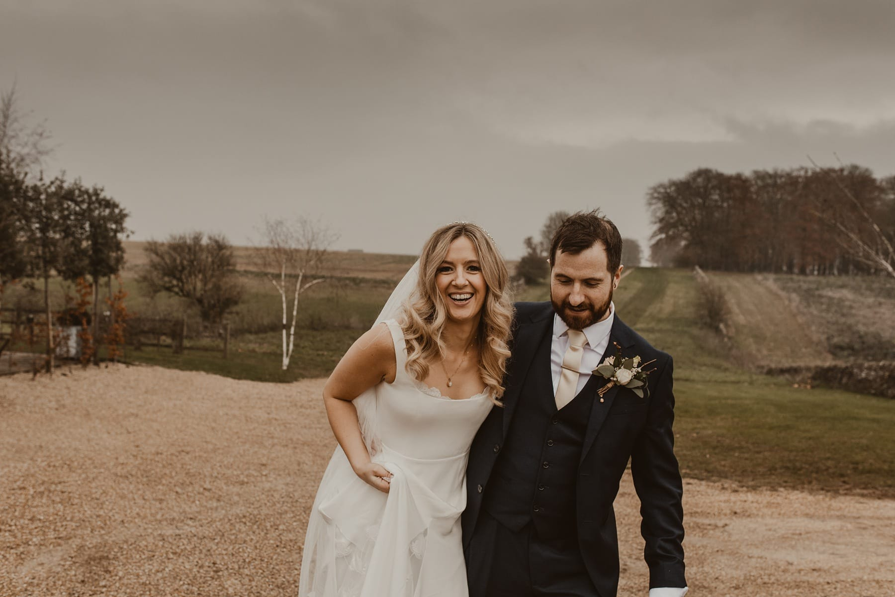 Bride and groom laughing, fields