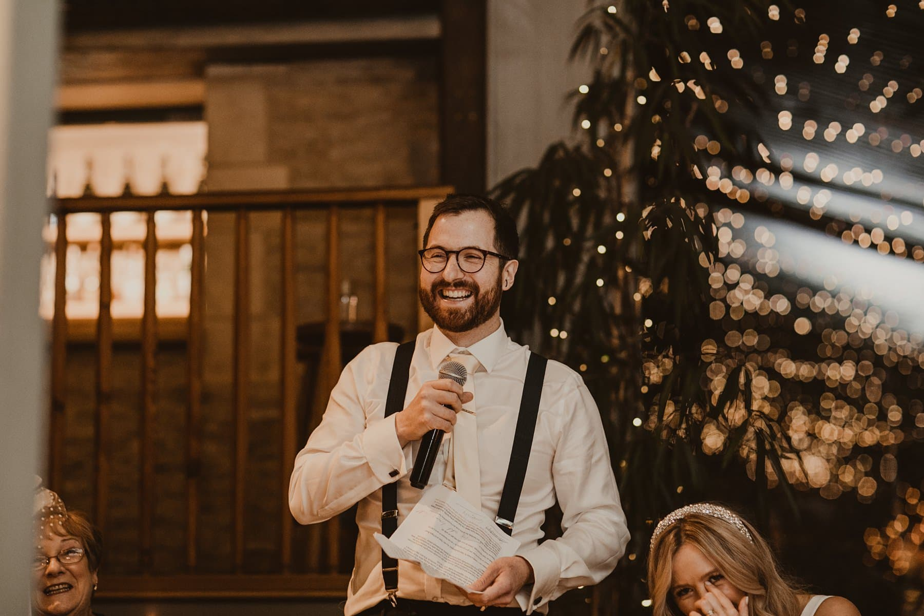 Groom laughing whilst doing his speech