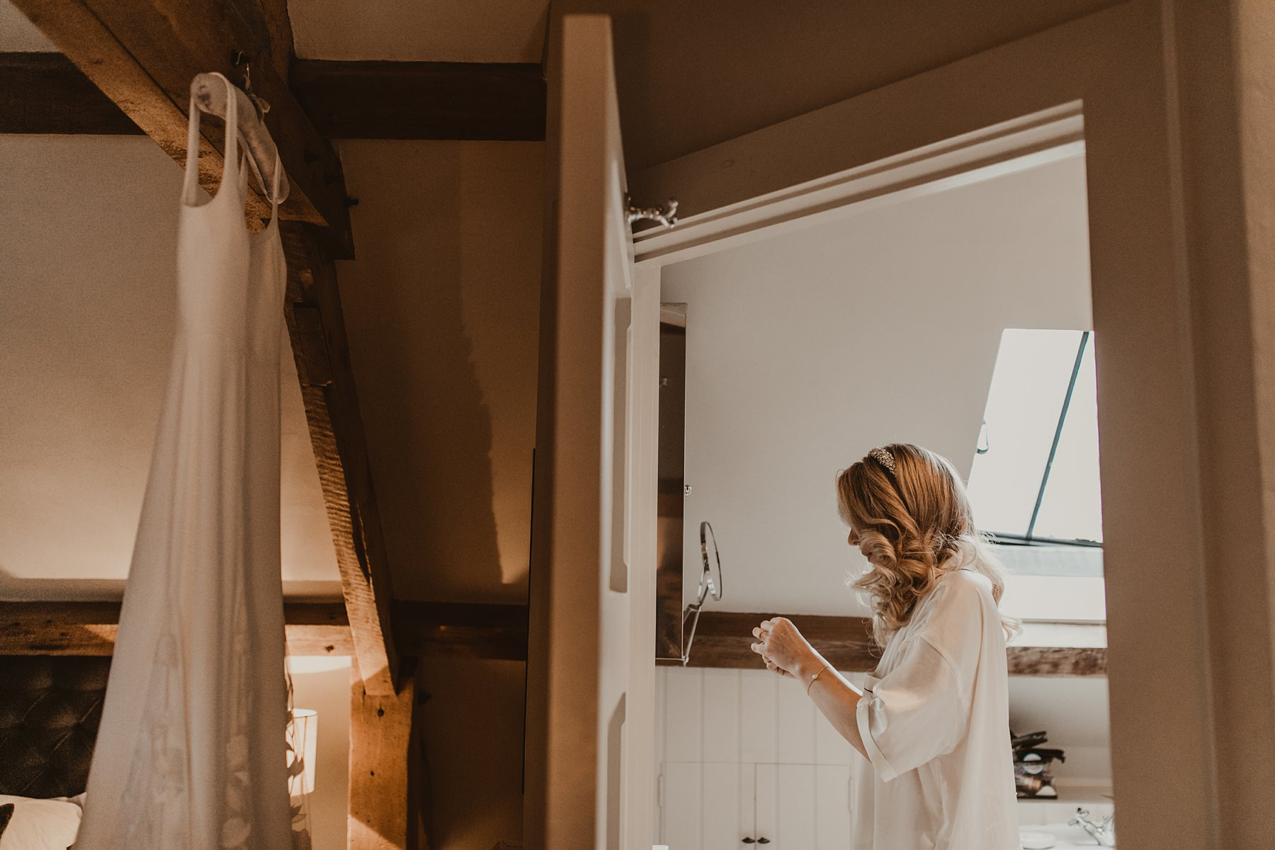 Bride putting on necklace in the mirror | Stone Barn Wedding