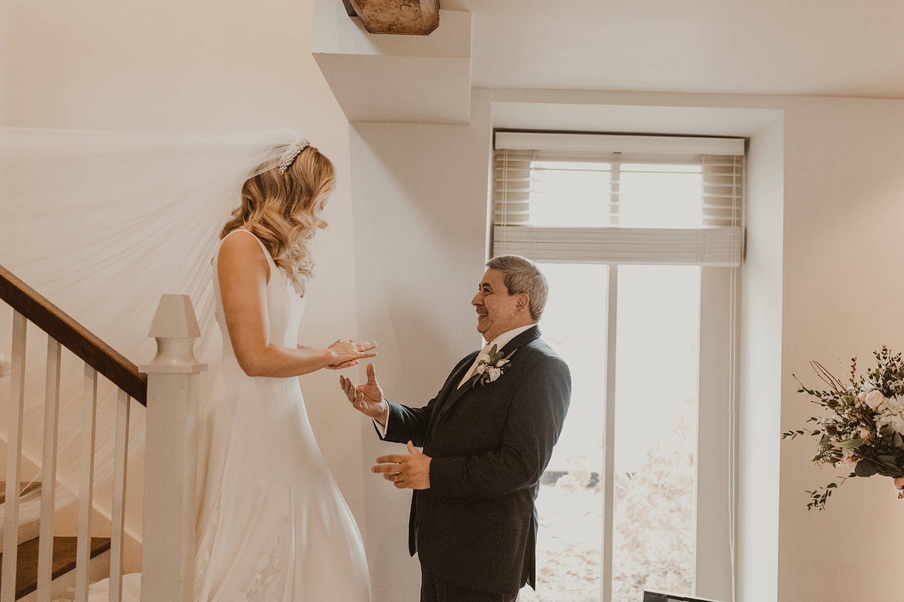 bride seeing dad at the bottom the stairs