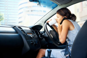 woman drinking coffee while driving distracted