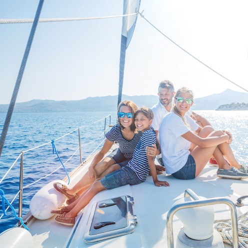 Happy family with adorable daughter and son resting on a big yacht