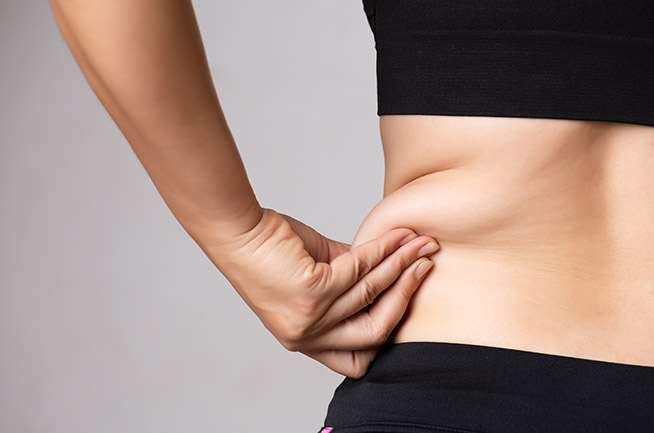 woman holding belly fat Bellava MedAesthetics and Plastic Surgery Center in Bedford Hills, NY