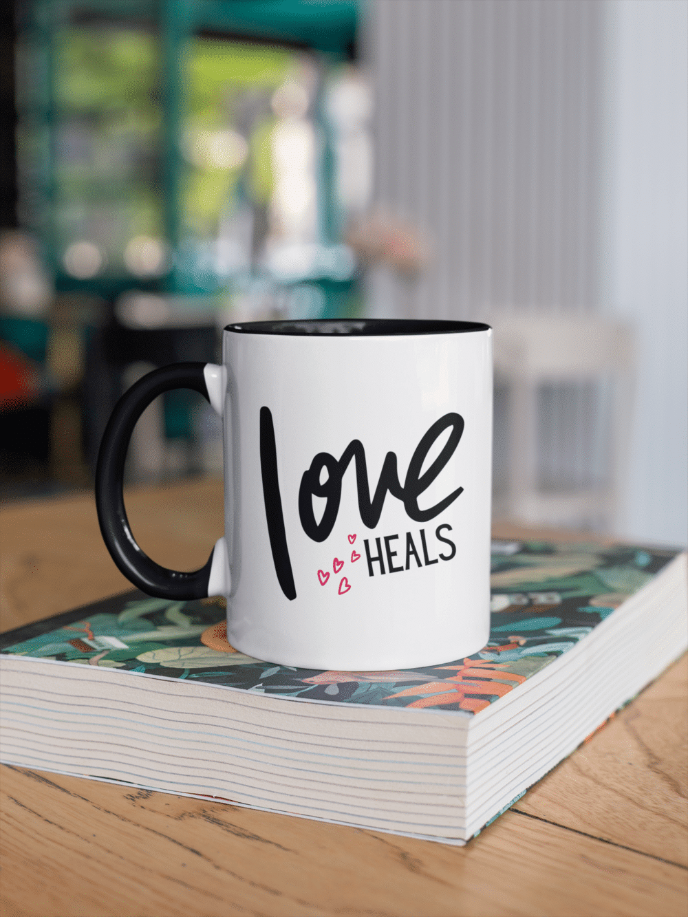 Love Heals black and white mug resting on a book in a cafe