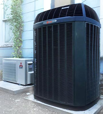 one ductless outdoor system next two an large outdoor central air condenser at a residential property