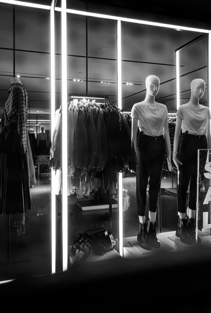 Dark black and white image of a woman's store, with floor lighting. around the bottom of a display with two models dressed in combat boots with white t-shirts.