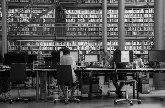 A black and white photo of people working at computers in a library.