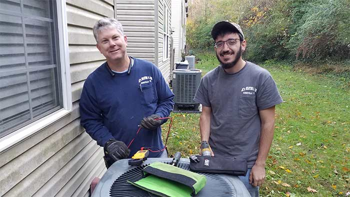 Jason Charkosky and a technician performing air conditioning repair