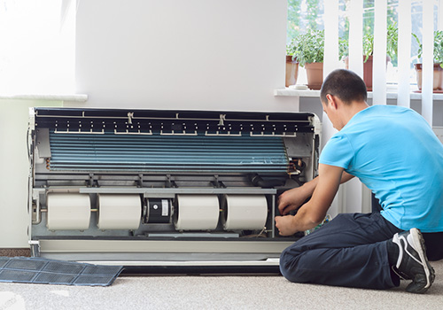 Man Fixing Residential Air Conditioner
