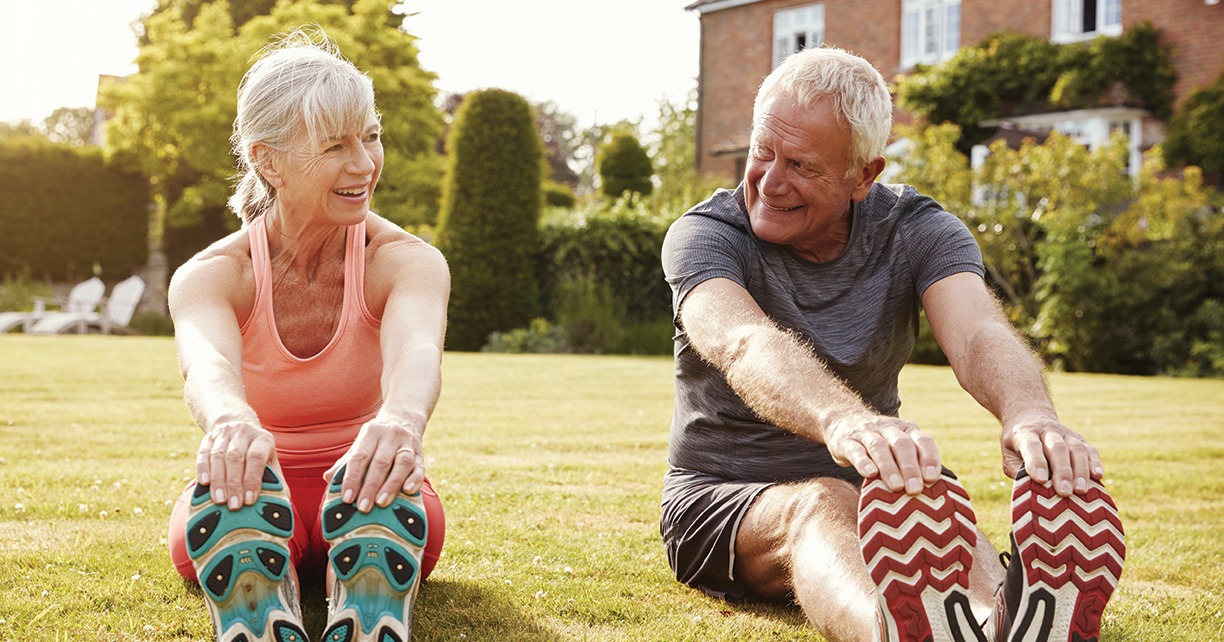 old couple stretching their legs and smiling outside