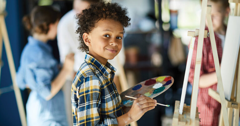 child smiling and painting