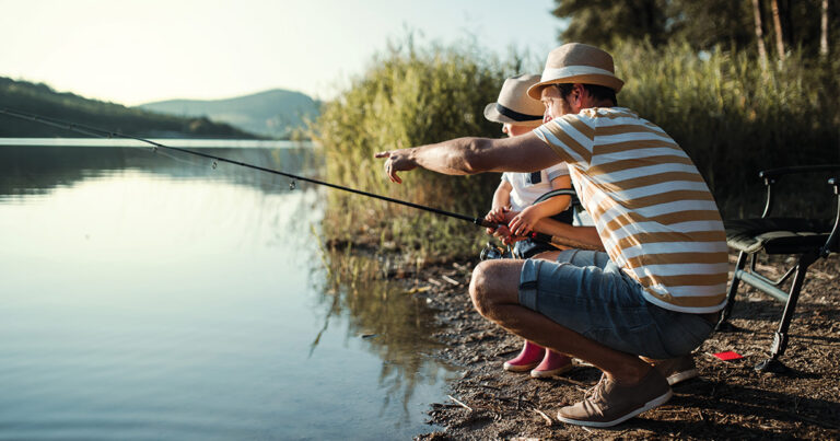 dad fishing outside by the water with son