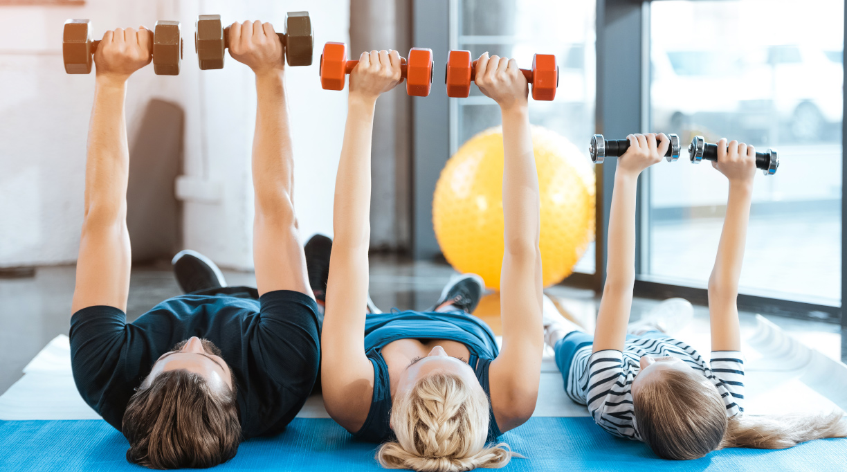 family laying down lifting small weights