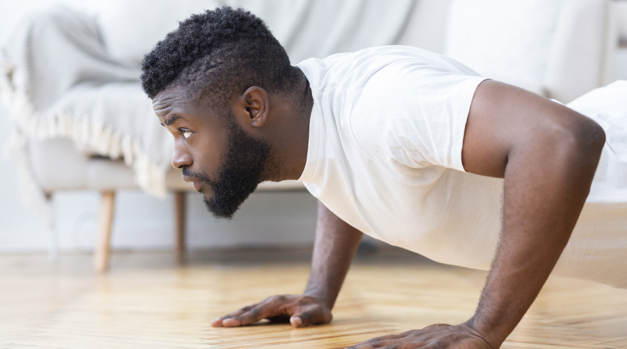 man doing a push up in a white shirt
