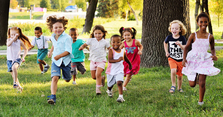 Children Running in the wooded grass during summer camp.