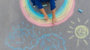 kids drawing a rainbow sun and rain clouds with chalk