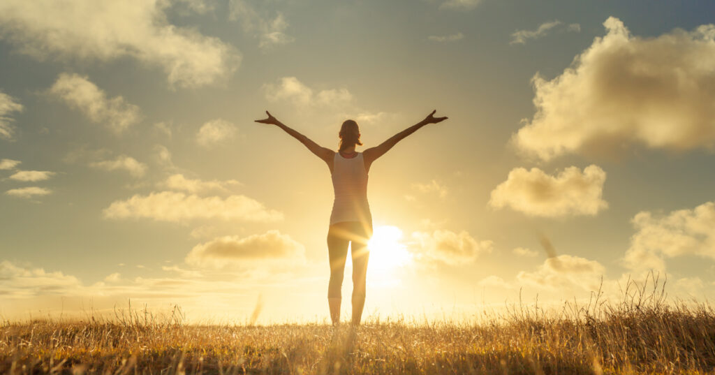 person with their arms up facing the sun outside in a field