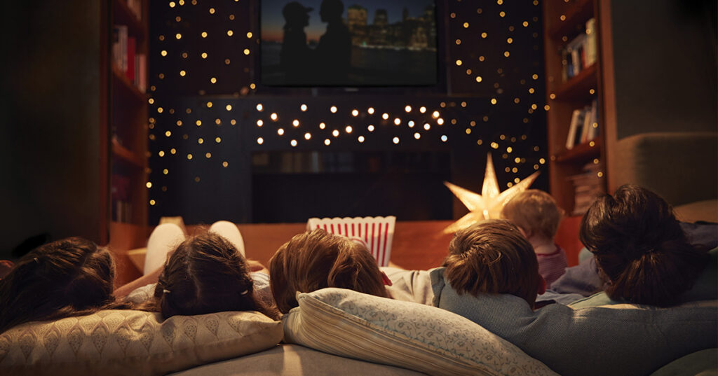 family laying on pillows watching a movie