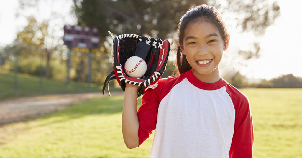 girl holding baseball in a mit on her hand