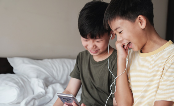 kids putting headphones in and watching their phone