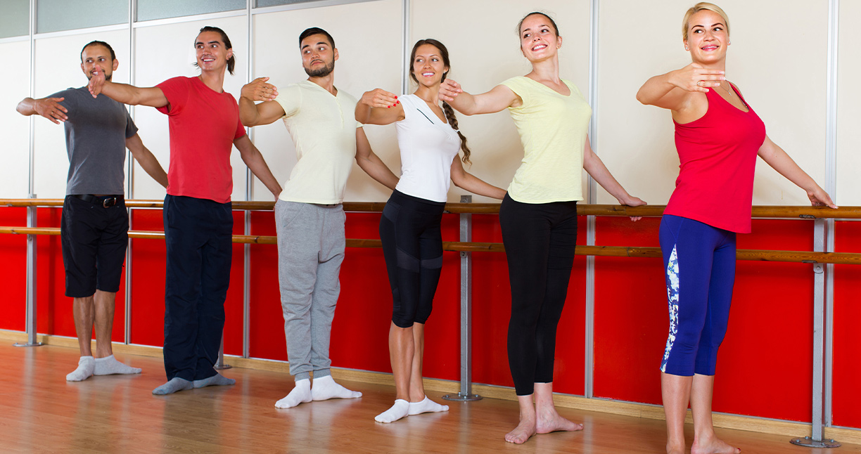 Group of men and women practicing at the ballet barre