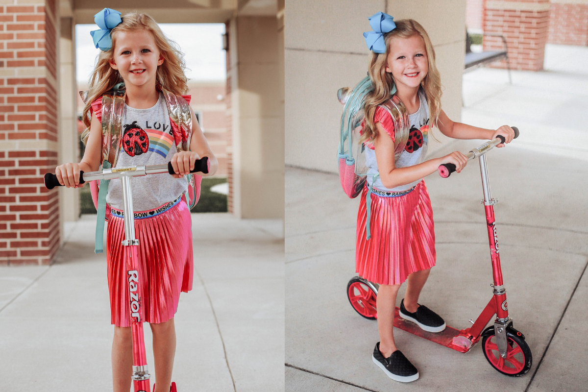 back to school girls outfit | Walmart Back To School Shopping by popular Florida fashion blog, Haute and Humid: image of a girl riding on her scooter in front of her school and wearing a Walmart 365 Kids From Garanimals Flutter Graphic Tank Top, 65 Kids From Garanimals Shimmer Foil Pleated Skirt, and Wonder Nation Solid and Printed Bike Shorts.