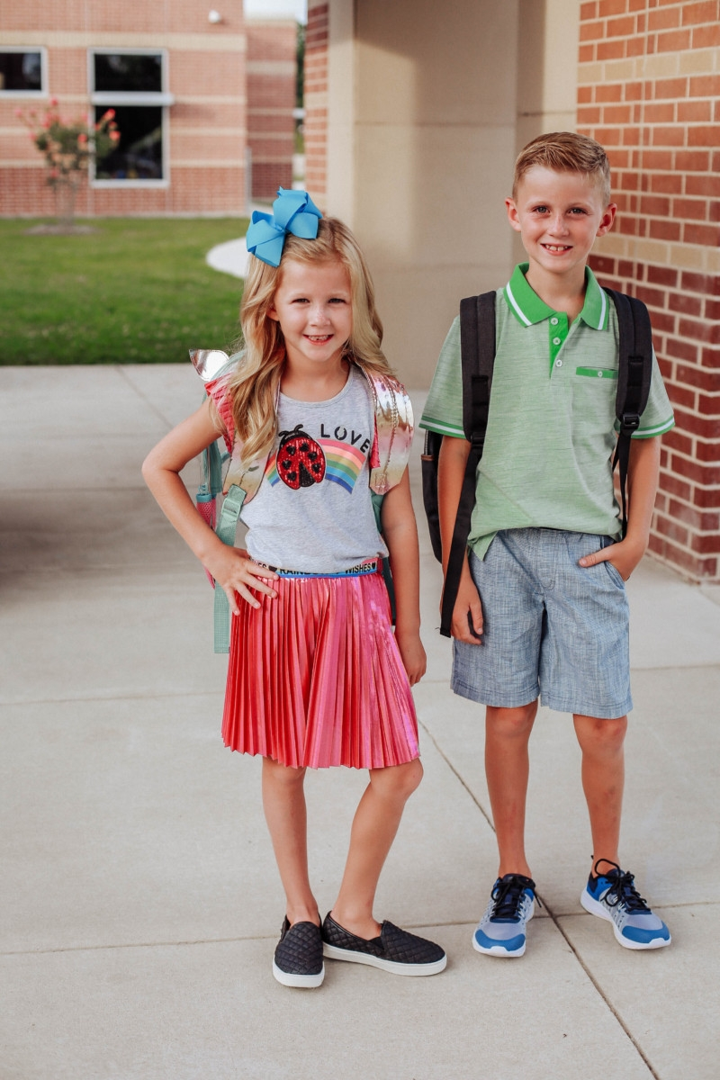 walmart back to school | Walmart Back To School Shopping by popular Florida fashion blog, Haute and Humid: image of a boy and girl standing next to each other outside of their school. The girls is wearing a Walmart 365 Kids From Garanimals Flutter Graphic Tank Top, 65 Kids From Garanimals Shimmer Foil Pleated Skirt, and Wonder Nation Solid and Printed Bike Shorts, 2-Pack. The boy is wearing Walmart Athletic Works Boys' Slip On Cage Athletic Shoes, green Wonder Nation Short Sleeve Stretch Jersey Polo, and Wonder Nation Rib Waist Pull on Short.