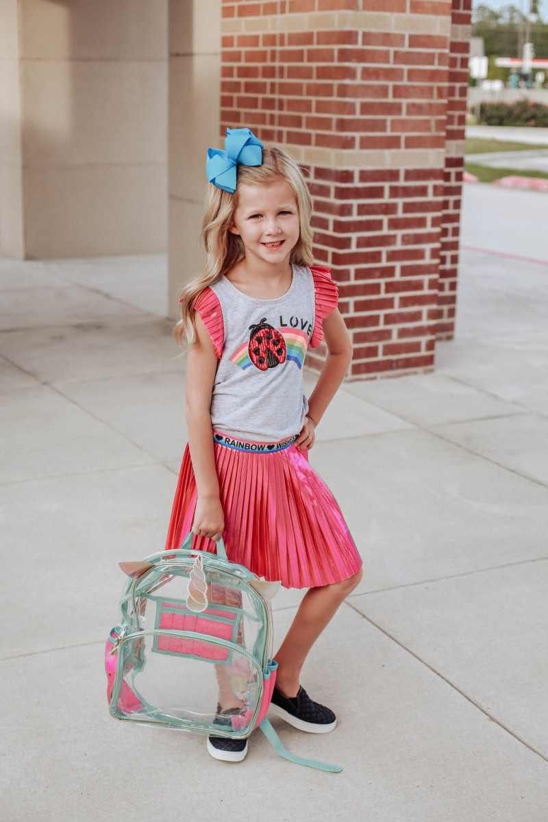 walmart back to school shopping | Walmart Back To School Shopping by popular Florida fashion blog, Haute and Humid: image ofa girl is wearing a Walmart 365 Kids From Garanimals Flutter Graphic Tank Top, 65 Kids From Garanimals Shimmer Foil Pleated Skirt, and Wonder Nation Solid and Printed Bike Shorts and holding a Wonder Nation Clear Kids Backpack.
