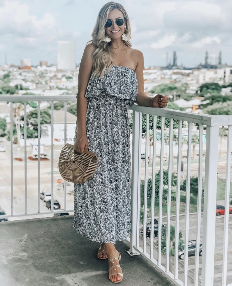 floral maxi dress | Amazon Prime Day 2019 by popular Houston life and style blog, Haute and Humid: image of a woman standing outside on a balcony and wearing a black and white Yidarton Women Summer Blue and White Porcelain Strapless Boho Maxi Long Dress.