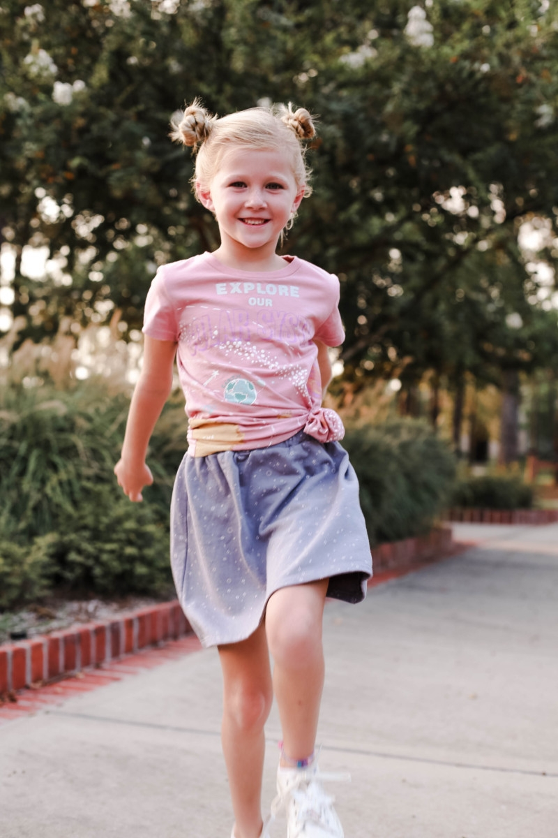 girls back to school outfit | How to Get to School on Time: 7 Easy Ways by popular Houston blog, Haute and Humid: image of a girl standing outside and wearing a Peek Aren't You Curious Solar System Graphic Tee, Peek Aren't You Curious Violet Skirt.