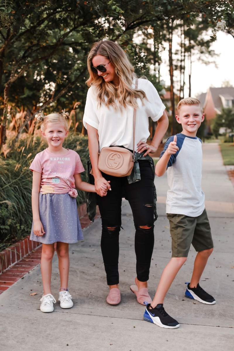 school on time | How to Get to School on Time: 7 Easy Ways by popular Houston blog, Haute and Humid: image of a mom and two kids standing outside and wearing a Peek Aren't You Curious Solar System Graphic Tee, Peek Aren't You Curious Violet Skirt, All in Favor Button Back Top, Madewell 9-Inch High Waist Skinny Jeans, Caslon Metallic Stitch Utility Jacket, Gucci Soho Disco Leather Bag, Tucker and Tate Baseball T-Shirt, Tucker and Tate Knit Shorts, and Nike Free Run 5.0 Sneaker.