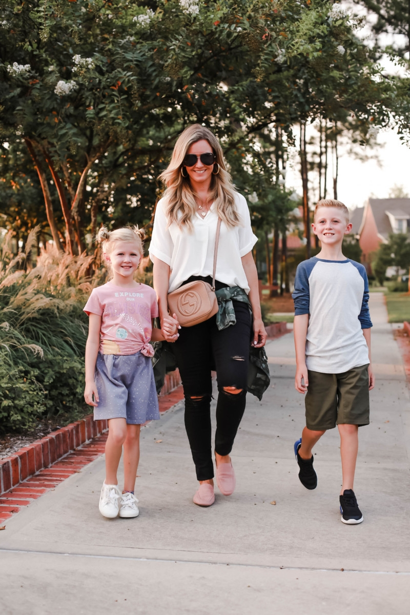 fall transition outfit | How to Get to School on Time: 7 Easy Ways by popular Houston blog, Haute and Humid: image of a mom and two kids standing outside and wearing a Peek Aren't You Curious Solar System Graphic Tee, Peek Aren't You Curious Violet Skirt, All in Favor Button Back Top, Madewell 9-Inch High Waist Skinny Jeans, Caslon Metallic Stitch Utility Jacket, Gucci Soho Disco Leather Bag, Tucker and Tate Baseball T-Shirt, Tucker and Tate Knit Shorts, and Nike Free Run 5.0 Sneaker.