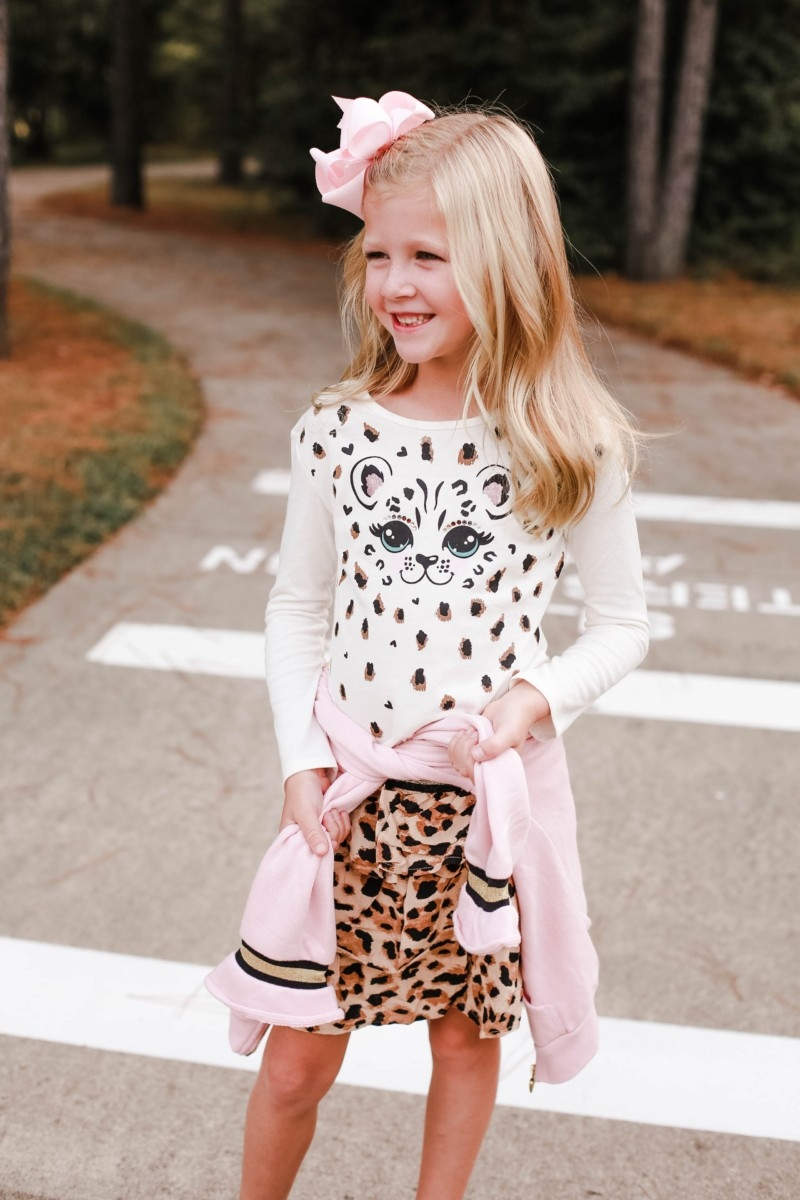 girls pink hoodie | Girls Animal Print fall Clothes | Walmart Fall Clothing: Girls Animal Print Favorites by popular Houston fashion blog, Haute and Humid: image of a girl walking her dog and wearing a Walmart 365 Kids From Garanimals Girls' Skort, Walmart black quilted sneakers, 365 Kids From Garanimals Cheetah Lined Hoodie with 3D Ears, and 365 Kids From Garanimals Girls' Long Sleeve Graphic T Shirt.