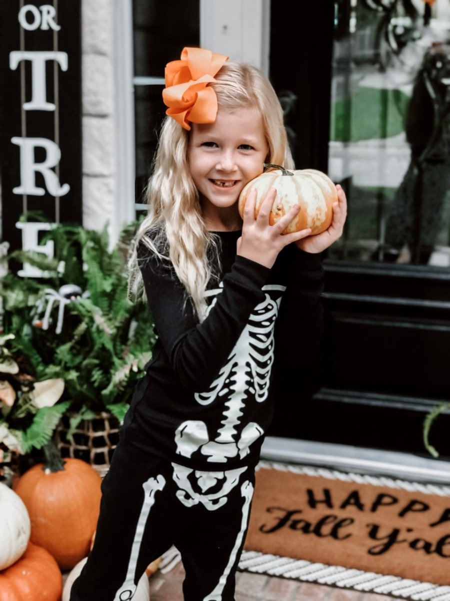 Halloween Treats | Easy Halloween Activities for Families by popular Houston lifestyle blog, Haute and Humid: image of a little girl holding pumpkins on a front porch with a Target Project 62 Chevron Woven Area Rug, Etsy Happy Fall Yall Welcome Doormat, and wearing Amazon Little Pajamas skeleton glow-in-the-dark pajama sets.