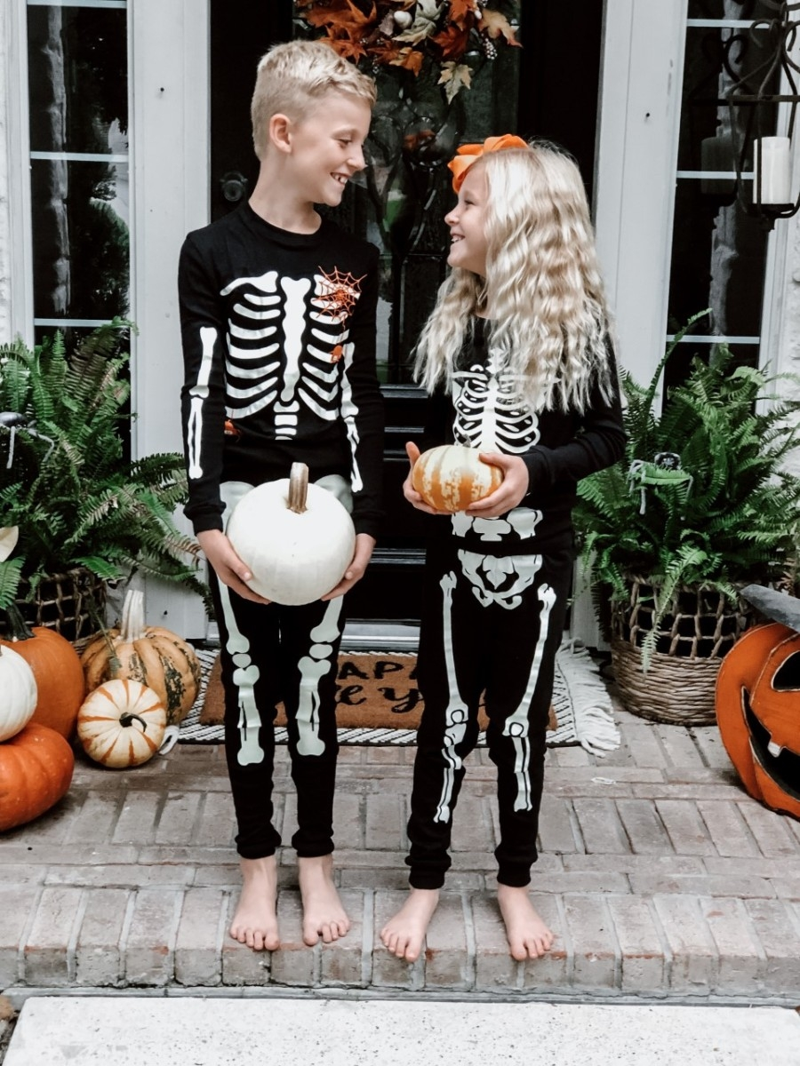kids Halloween pajamas | Easy Halloween Activities for Families by popular Houston lifestyle blog, Haute and Humid: image of two kids holding pumpkins on a front porch with a Target Project 62 Chevron Woven Area Rug, Etsy Happy Fall Yall Welcome Doormat, and wearing Amazon Little Pajamas skeleton glow-in-the-dark pajama sets.