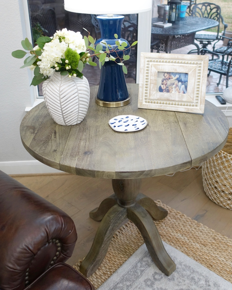 end table | Living Room Makeover by popular Houston lifestyle blog, Haute and Humid: image of a remodeled living room with coffee table containing a white flower vase, wood picture frame, and blue lamp.