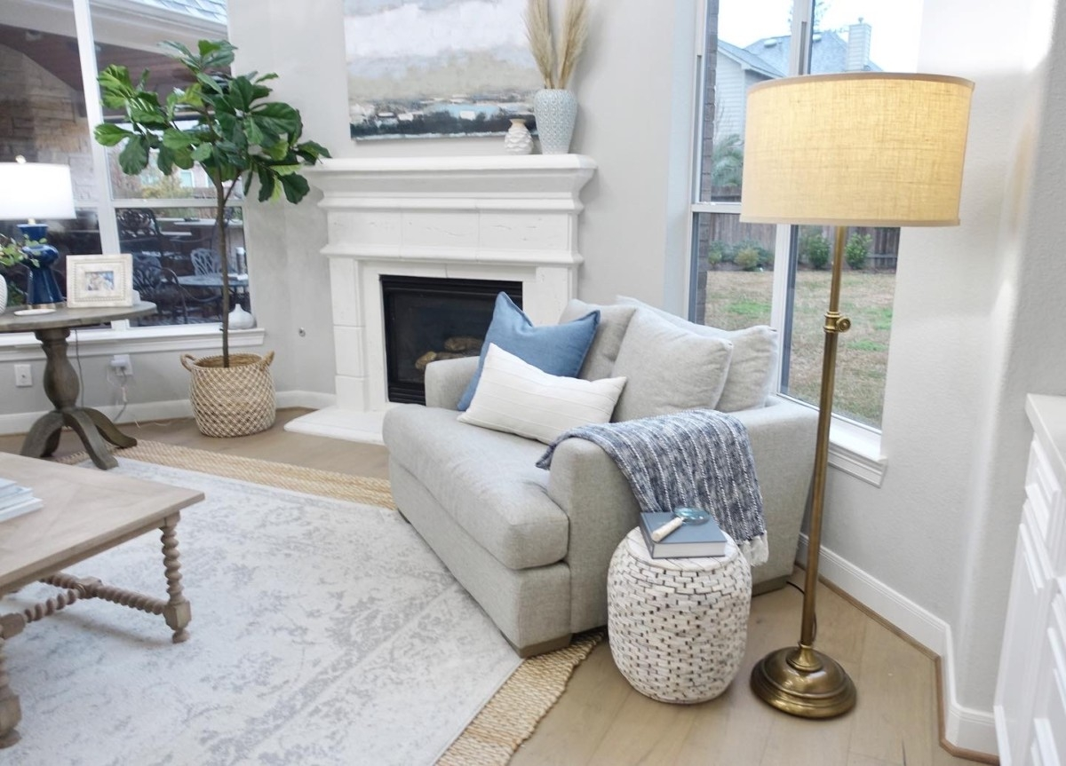 chair and a half | Living Room Makeover by popular Houston lifestyle blog, Haute and Humid: image of a remodeled living room with a Wayfair Shayla 20-Light Candle Style Wagon Wheel Chandelier, Wisteria Barley Twist Coffee Table, and Perigold ARIANA VERNAY RECTANGULAR CONSOLE TABLE.