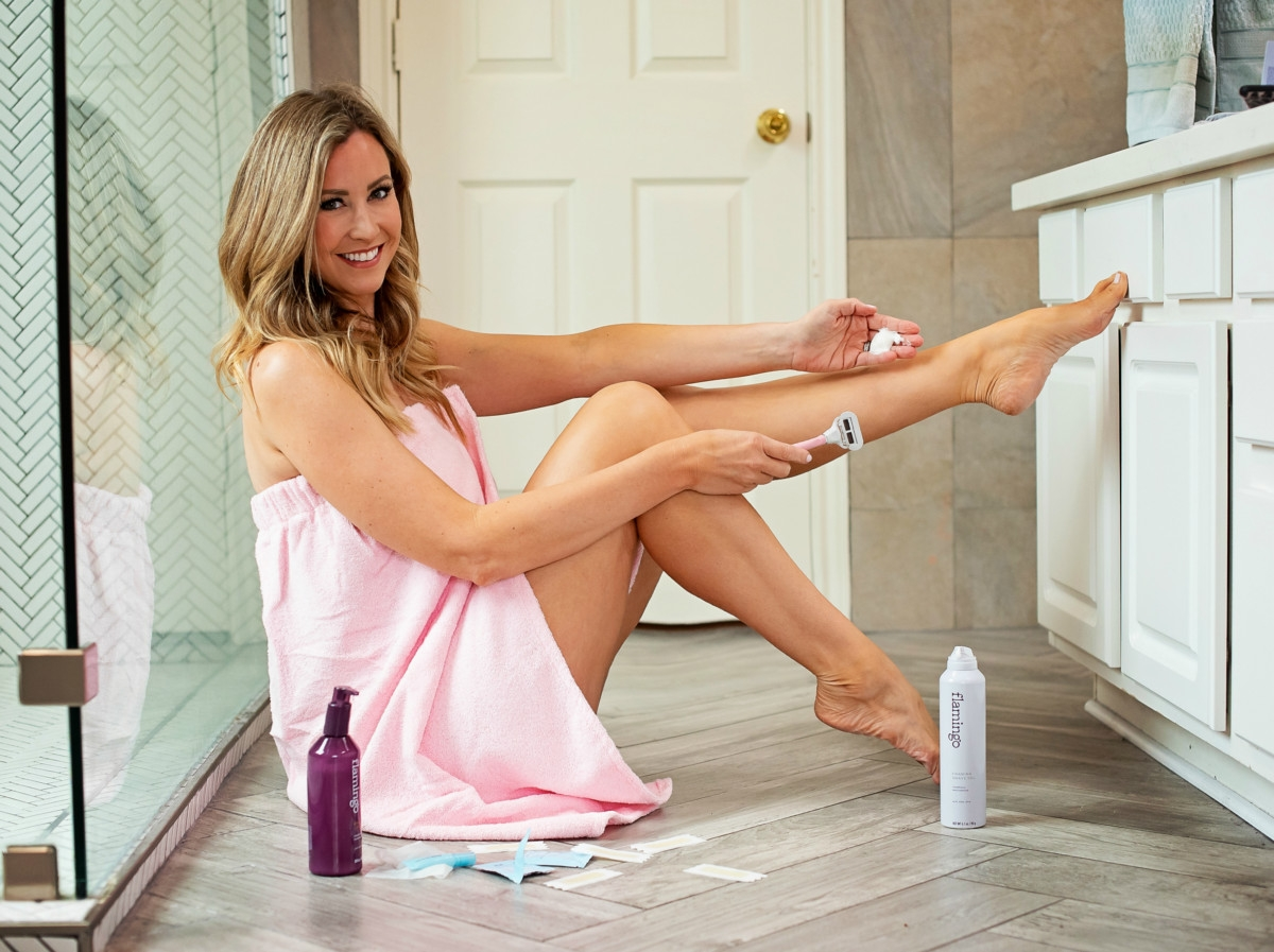 Flamingo Razor by popular Houston lifestyle blog, Haute and Humid: image of a woman sitting on her bathroom floor and shaving her legs with the Flamingo razor.